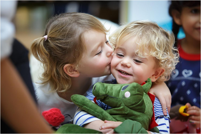 cute girl kissing young baby holding cuddly toy