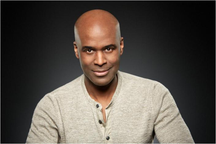 black male studio headshot against backdrop