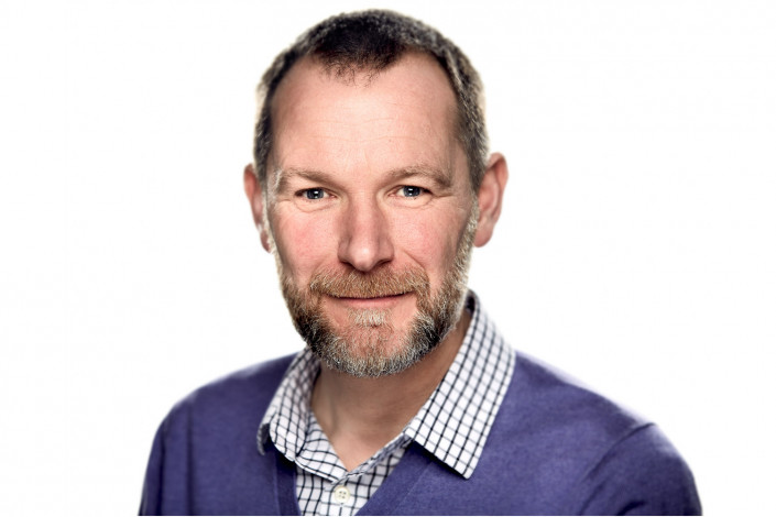 man in studio headshot against white backdrop
