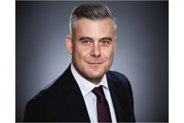 stylish man in studio headshot against grey backdrop