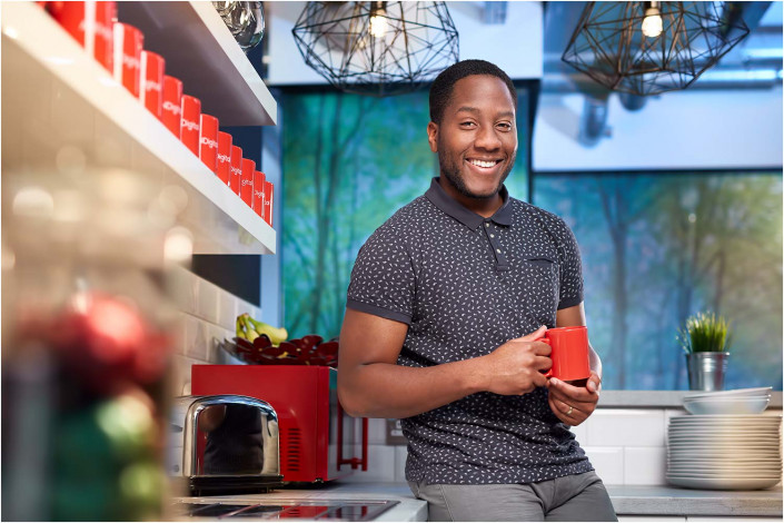 black man leaning against counter top holding cup of tea
