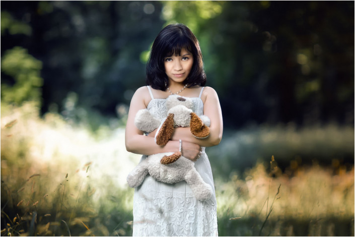 pretty girl with cuddly toy in field