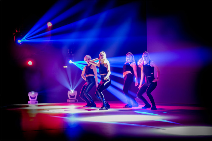 dancers on stage with colourful lighting
