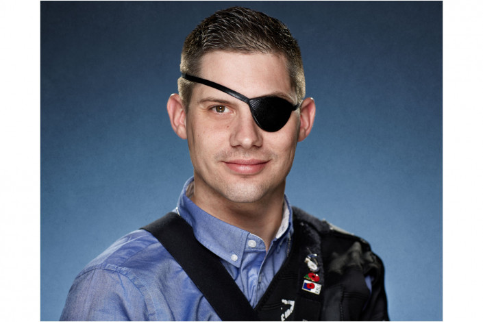 man with eye patch in studio headshot against blue backdrop