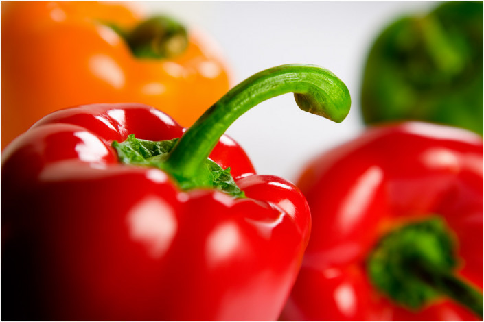 food photography of multi-coloured peppers against white