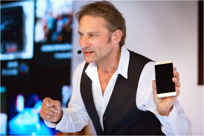 man on stage holding phone speaking to conference delegates