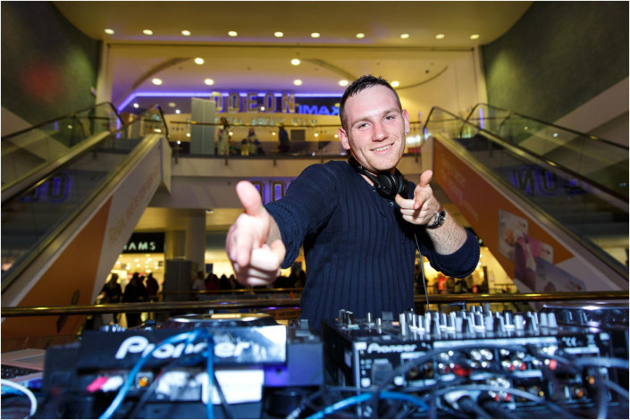 DJ entertainer at shopping centre event and pointing to camera