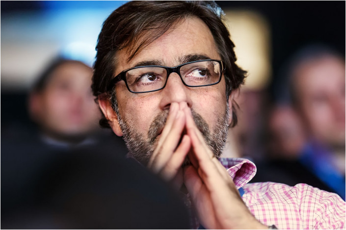 man thinking hard in audience at a conference