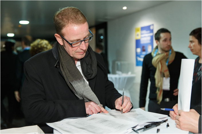 man signing in at a conference