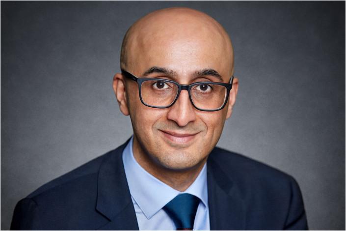 executive business headshot against grey backdrop