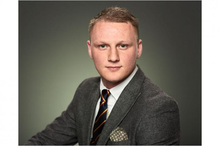 man in studio headshot against dark backdrop