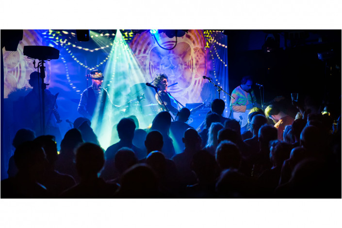 band on stage with coloured lighting