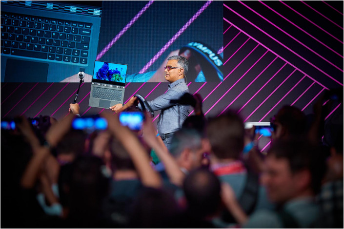 man holding laptop on stage at lenovo conference