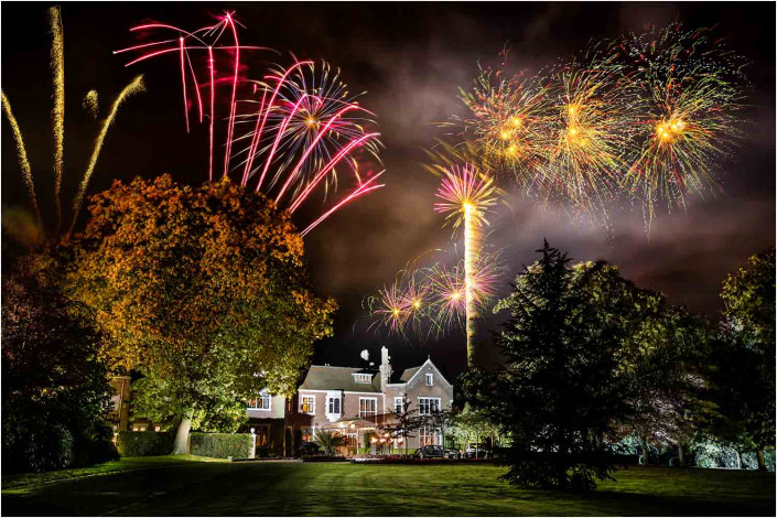 fireworks with large house in the foreground