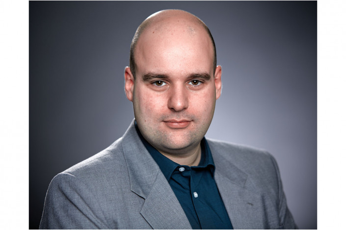 executive studio headshot against grey backdrop