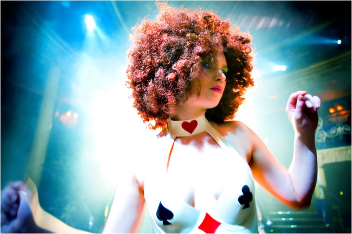 dancer with ginger afro against light beams