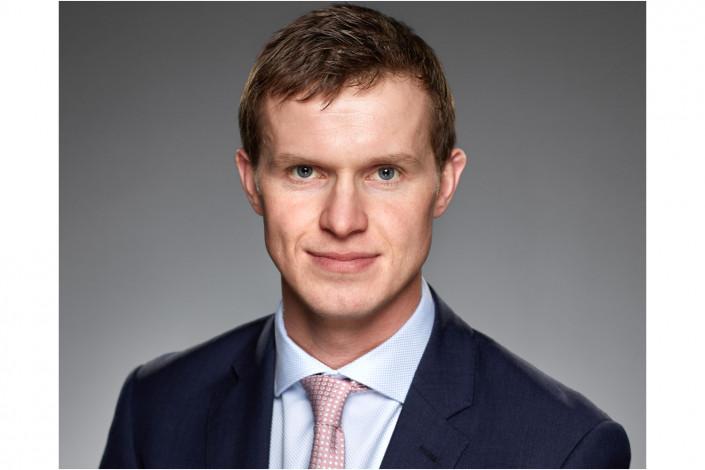 executive male studio headshot against grey backdrop