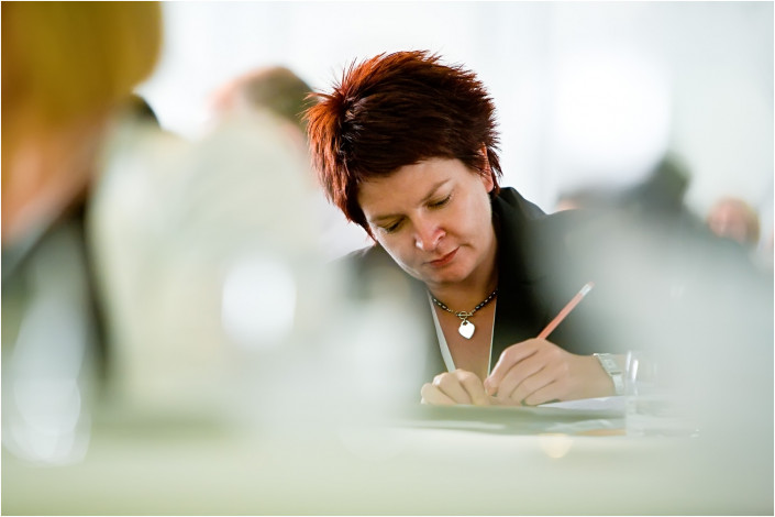 lady making notes at a conference
