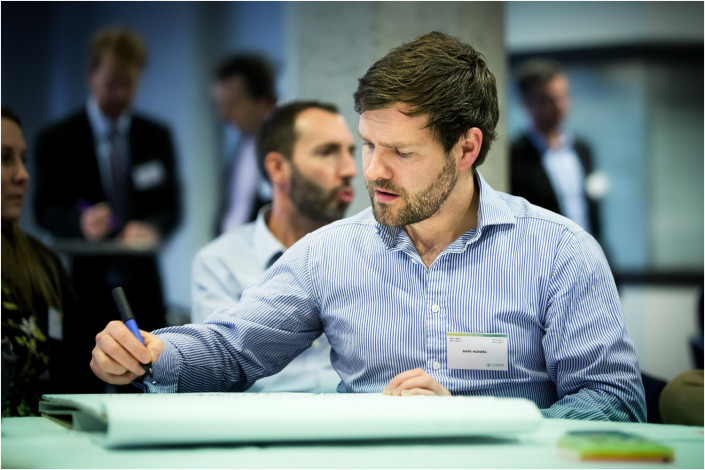 man making notes at a conference