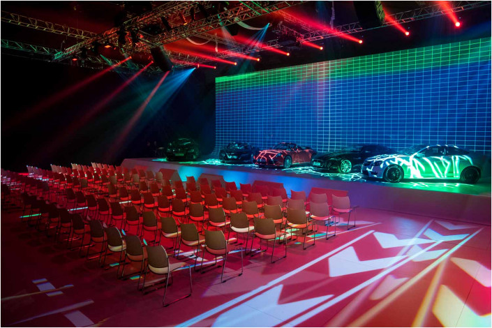 wide image of empty conference venue with cars on stage