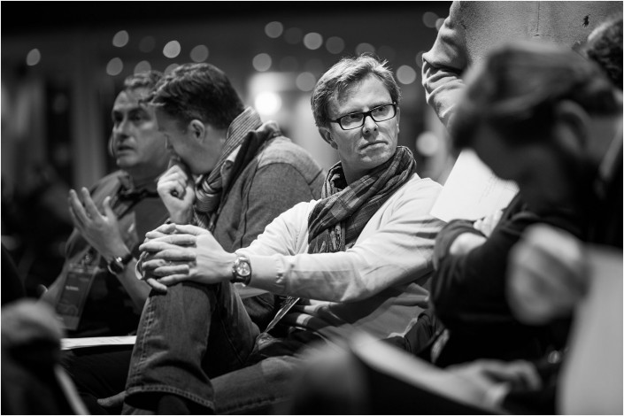 man in crowd listening to a colleague