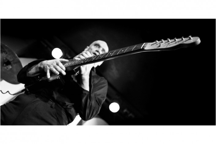 wilko johnson singer at a concert holding his guitar