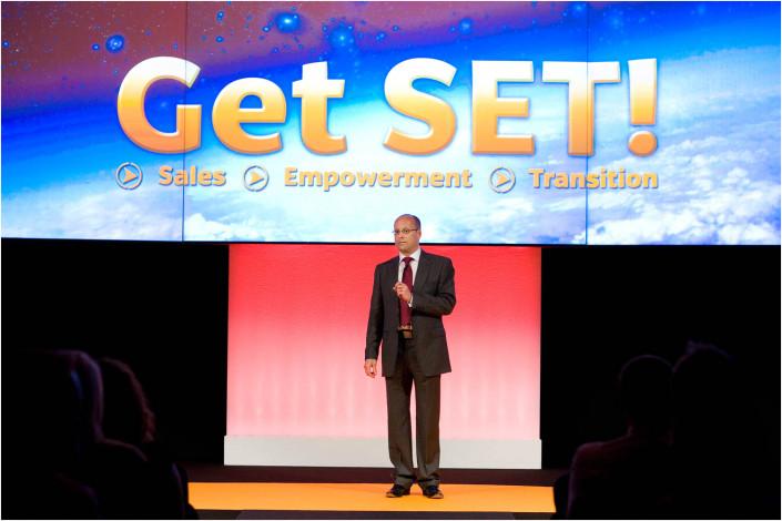 "speaker on big stage with ""get set"" logo behind him"