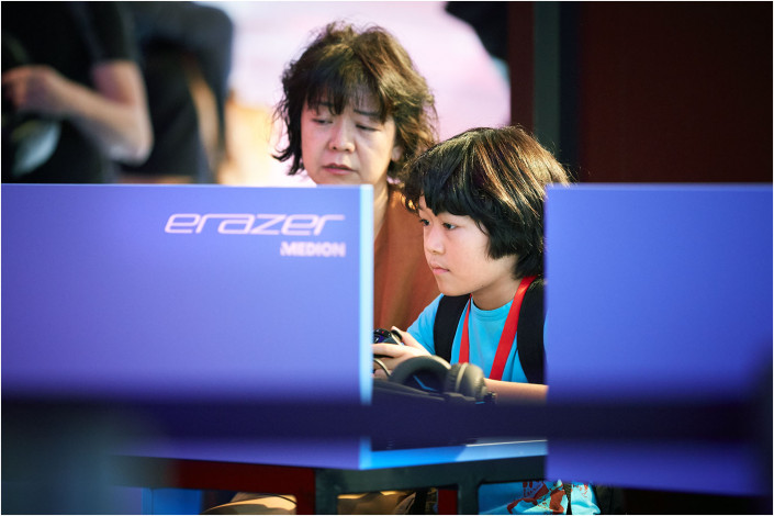 child operating a games computer at a tech show